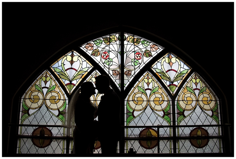 wedding couple silhouette by stained glass window at the lantern church calgary