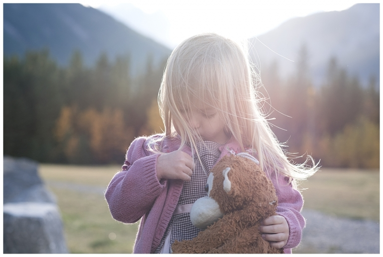 Girl with her stuffie in the wind in Canmore